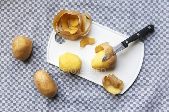 Geschälte und ungeschälte rohe Kartoffeln — Stockfoto