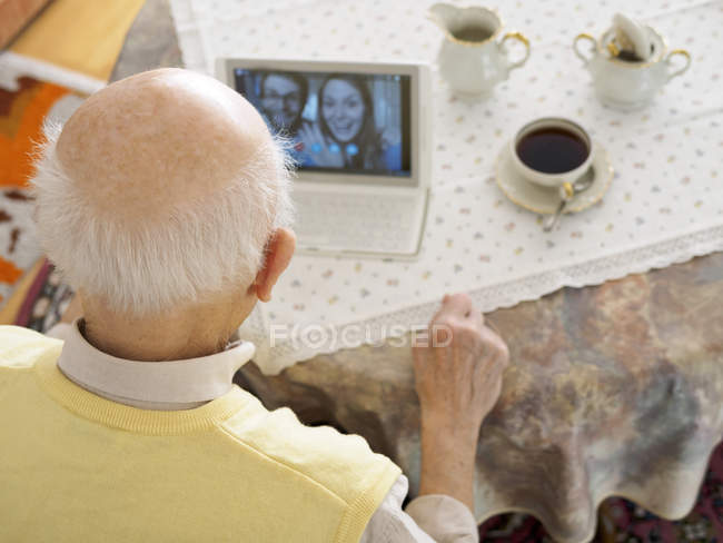 Grandfather videoconferencing with grandchildren with digital tablet — Stock Photo
