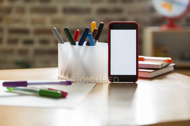 Смартфон на дерев'яний стіл з різнокольоровими фломастери дитяча кімната — стокове фото