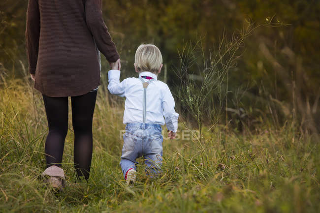 Mother with son walking on meadow — Stock Photo