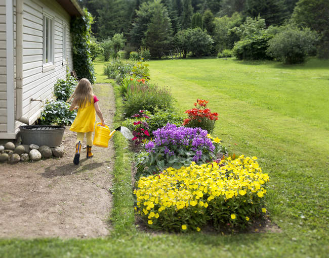 Girl walking with watering can on pathway near house — Stock Photo