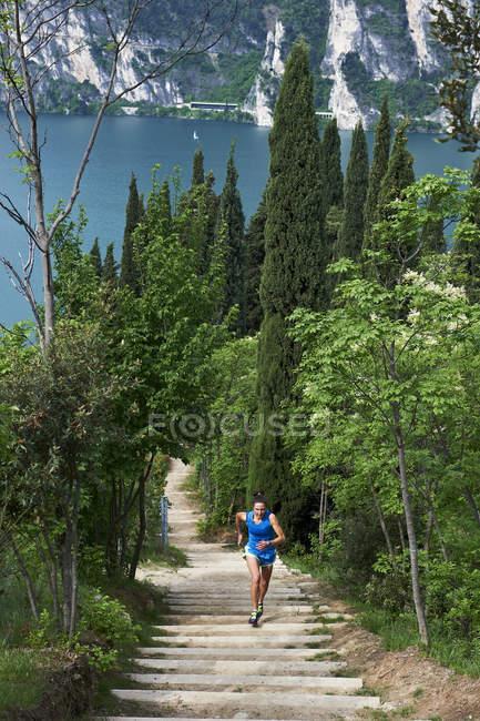 Mujer corriendo en las escaleras en el lago de Garda - foto de stock