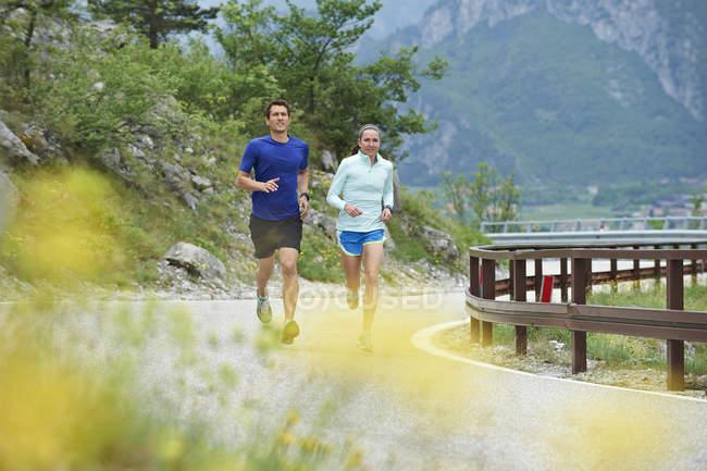 Couple running on road — Stock Photo