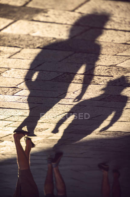 Italy, Venice, shadows of people on the pavement in morning light — Stock Photo