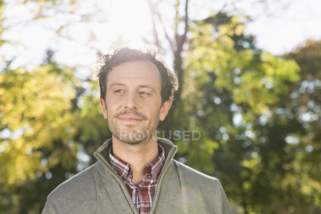 Portrait of smiling man standing at backlit — Stock Photo