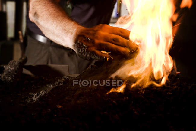 Blacksmith at work at the fireplace, closeup view of male hands — Stock Photo