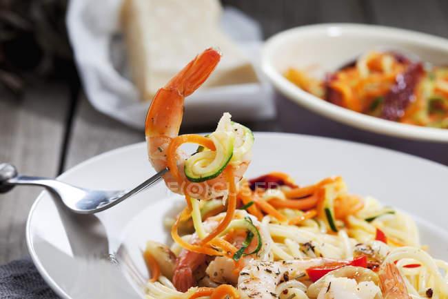 Спагетти с каракатицу и овощами на плите, спирали морковь и цуккини, вилка, макро — стоковое фото