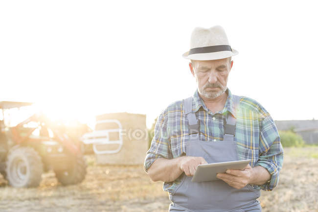 Farmer with digital tablet on field — Stock Photo