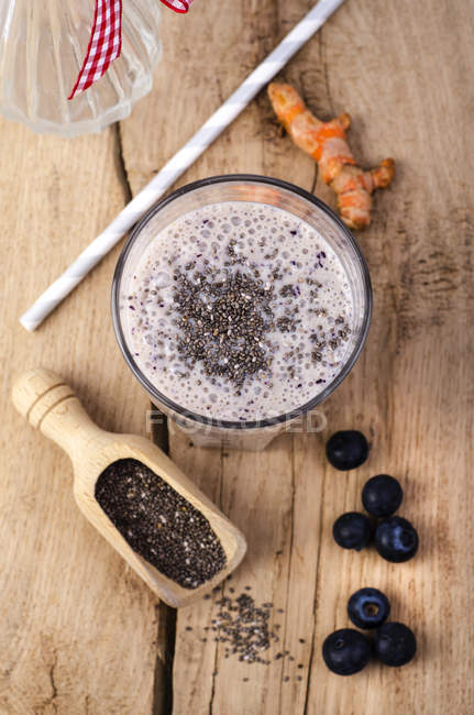 Bicchiere di frullato di mirtillo con pala di legno di semi di chia, curcuma e mirtilli su legno — Foto stock