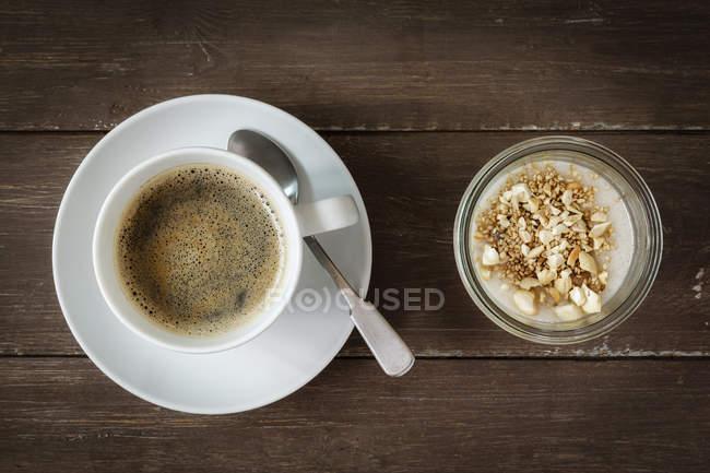 Чашка кофе и стекла веганский кокосовые пудинг с бананом и тапиоки гранулы — стоковое фото
