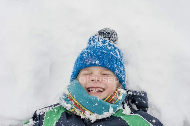 Overhead view of  happy boy lying in snow — Stock Photo
