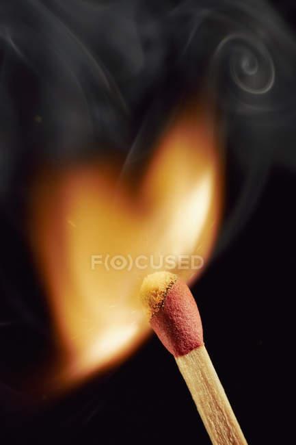 Burning matchstick on black background — Stock Photo