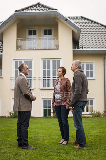 Estate agent communicating with potential buyers in front of residential house — Stock Photo