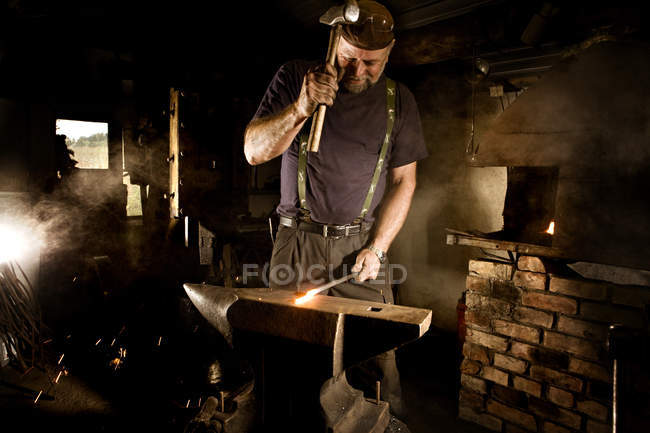 Blacksmith working with hammer at anvil — Stock Photo