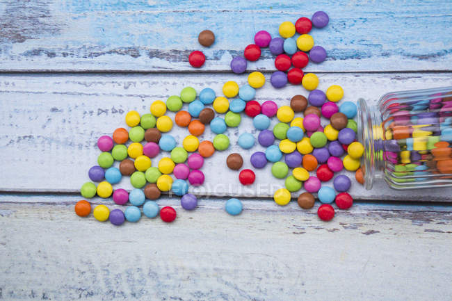 Smarties e barattolo di caramelle sulla superficie di legno azzurro — Foto stock