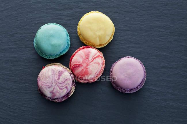 Fünf verschiedene Macarons auf Schiefer — Stockfoto
