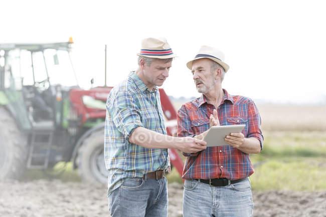 Zwei Bauern mit digital-Tablette diskutieren auf Feld — Stockfoto