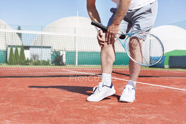 Тенісист з коліном біль на суд, низький розділ подання — стокове фото