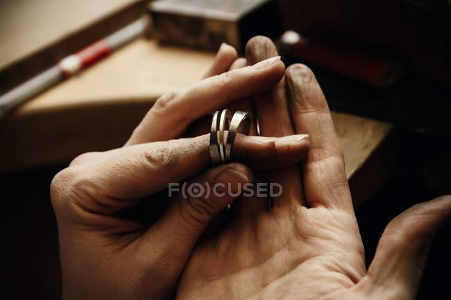 Goldschmied arbeitet an Eheringen, Hand hält unfertigen Ring — Stockfoto