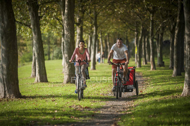 Family riding bicycles on path in park — Stock Photo