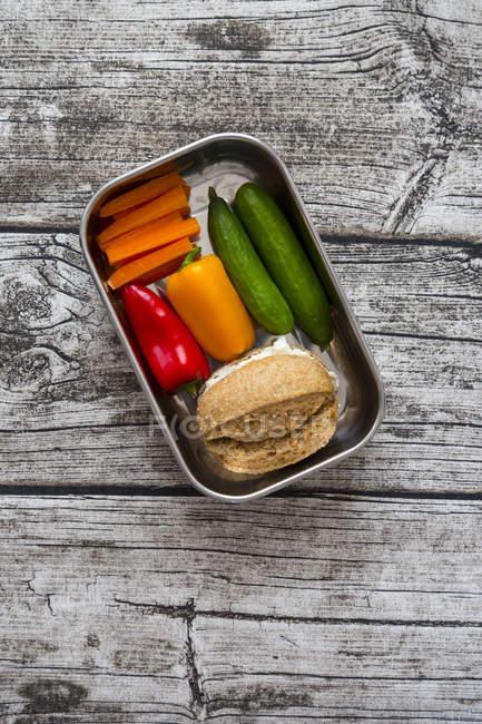 Ролл со сливочным сыром и морковью, перец и огурцы в металлической коробке — стоковое фото