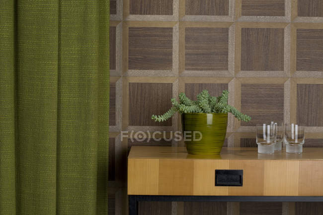 Sideboard with glasses and potted plant in front of wooden wall cladding — Stock Photo