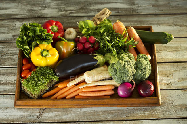 Wooden tray with different vegetables on wood — Stock Photo