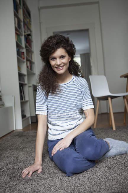 Giovane donna sorridente a casa seduto sul tappeto — Foto stock