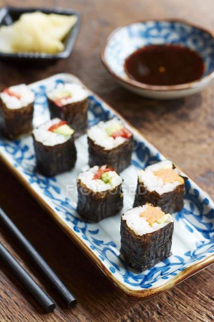Овощные суши, заполнены с сладкий картофель, морковь, авокадо и перец служил на узорные плиты с соевым соусом — стоковое фото