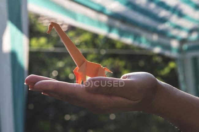 Orange origami giraffe on hand — Stock Photo
