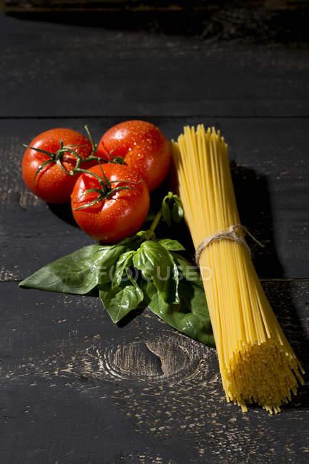 Spaghetti, basil and tomatoes on dark wood — Stock Photo