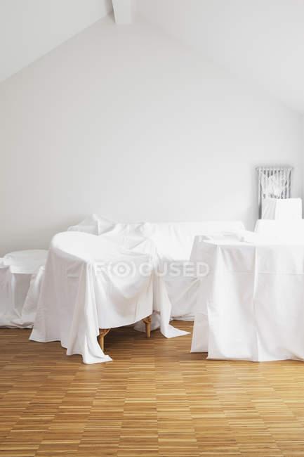 Vista diurna de muebles cubiertos con tela blanca en ático - foto de stock