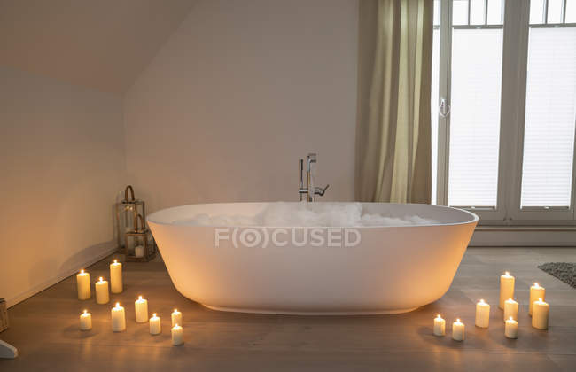 Modern bathtub with lighted candles arround — Stock Photo