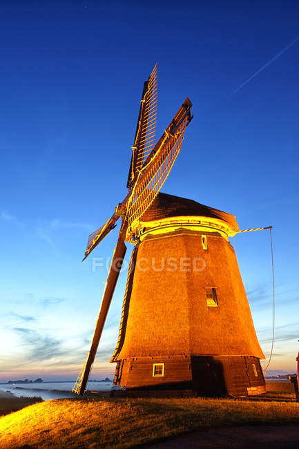 Netherlands, North Holland, windmill at dusk against sky — Stock Photo