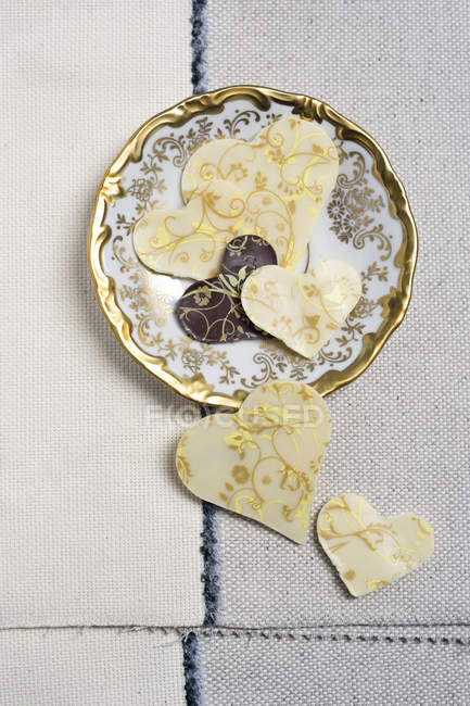 Homemade chocolate hearts with vintage plate on fabric — Stock Photo
