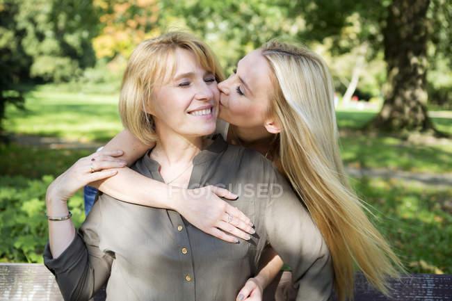 Дорослі дочки цілуватися матері в парку — стокове фото