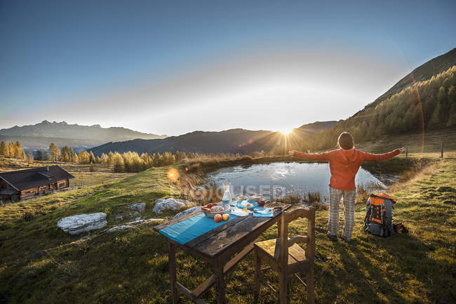 Austria, Altenmarkt-Zauchensee, young woman standing in the mountains at sunrise — Stock Photo
