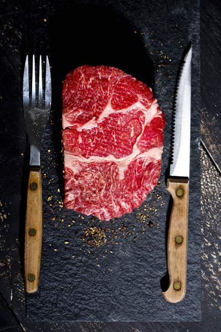 Rohes Rindfleischsteak und Pfeffer auf Schiefer mit Messer und Gabel — Stockfoto