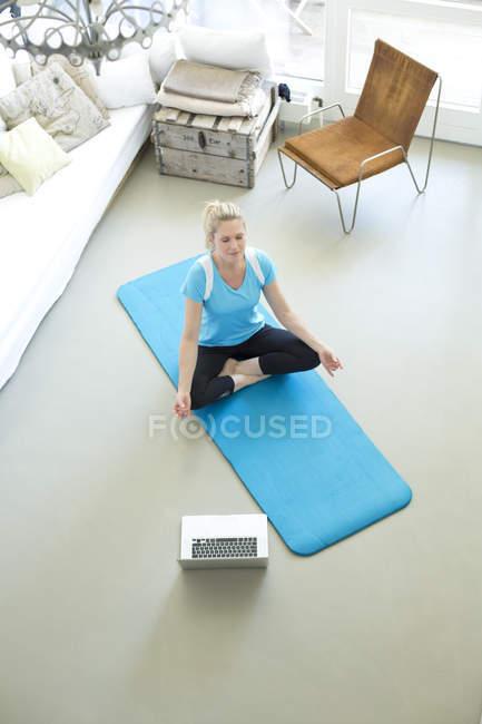 Donna con computer portatile che pratica yoga — Foto stock