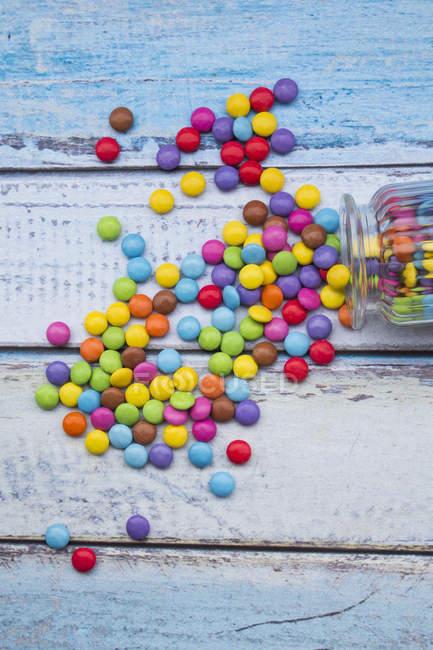 Smarties y tarro de caramelo en madera azul claro - foto de stock