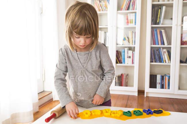 Девочка вырезает желтую модельную глину — стоковое фото