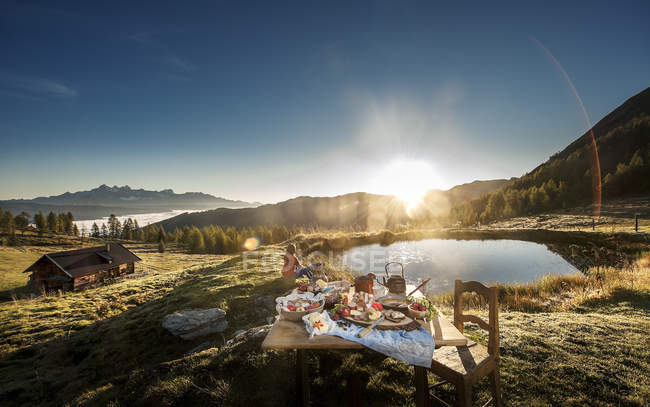 Austria, Salzburg State, Altenmarkt-Zauchensee, alpine pasture, breakfast at sunrise with woman sitting on background — Stock Photo