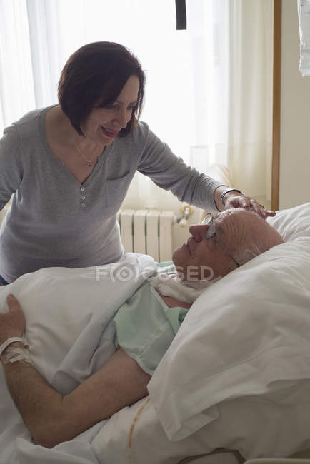Senior woman caring for husband in hospital recovering after surgery — Stock Photo