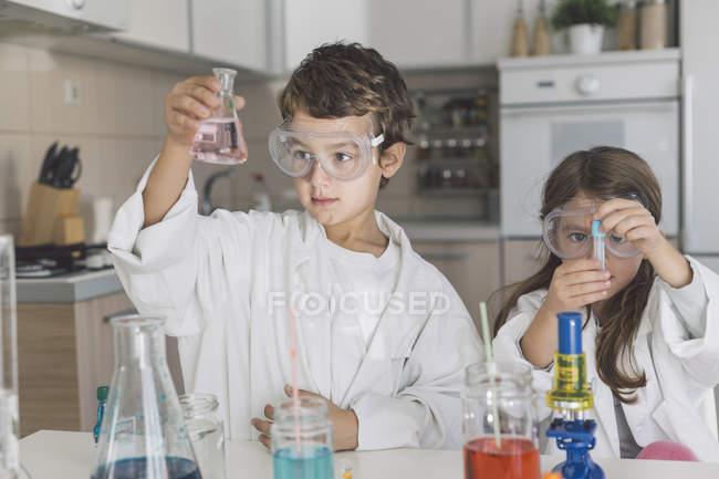 Мальчик и девочка играют в научные эксперименты дома — стоковое фото