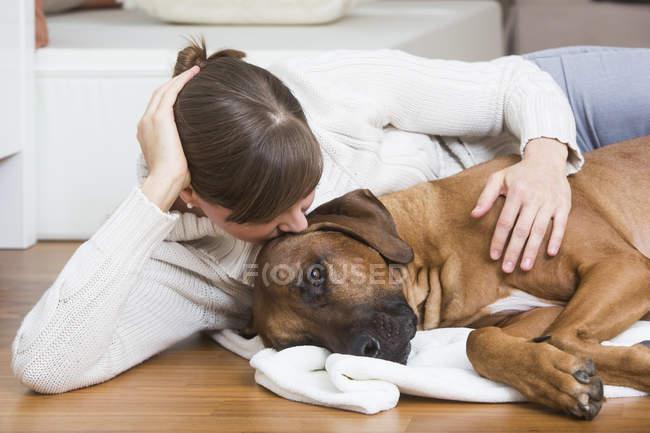 Жінка ласкавим її собака родезійськими ріджбек — стокове фото