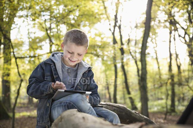 Deutschland, lächelnder kleiner Junge mit digitalem Tablet im Wald — Stockfoto