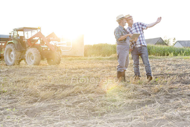 Zwei Bauern mit digital-Tablette auf Stoppelfeld diskutieren — Stockfoto