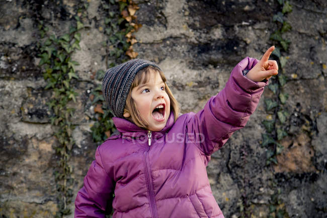 Excited girl wearing woolly hat and pink winter jacket pointing at something — Stock Photo