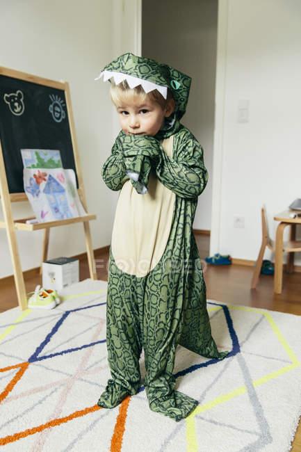 Ritratto di bambino che indossa un costume da dinosauro a casa — Foto stock