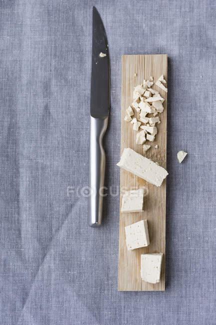 Tofu affettato su tavola di legno e coltello da cucina su stoffa — Foto stock